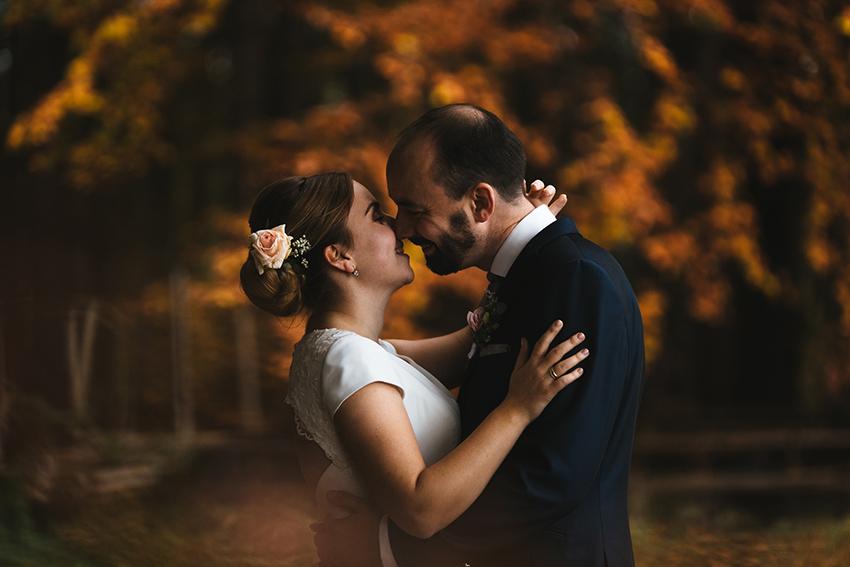 Brautpaar küsst sich fast im Portrait vor orangefarbenem Herbstlaub
