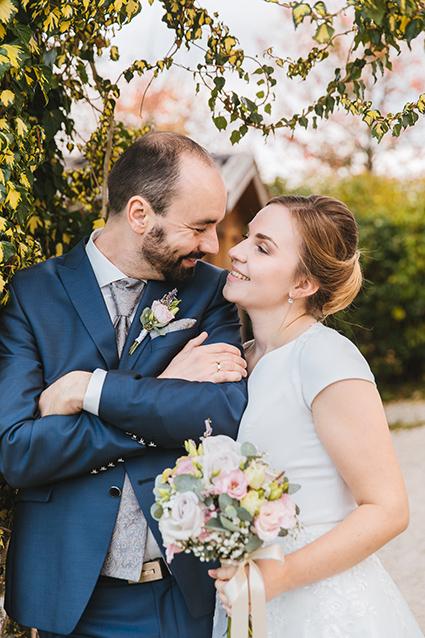Brautpaar lacht sich an, Bräutigam lehnt an einer Wand