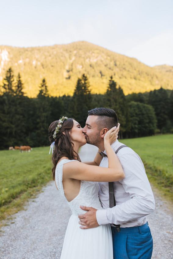 Brautpaar küsst sich mit Wald im Hintergrund