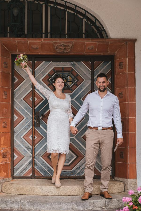 Brautpaar jubelt nach ihrer Trauung vor der Tür vom Rathaus Schliersee