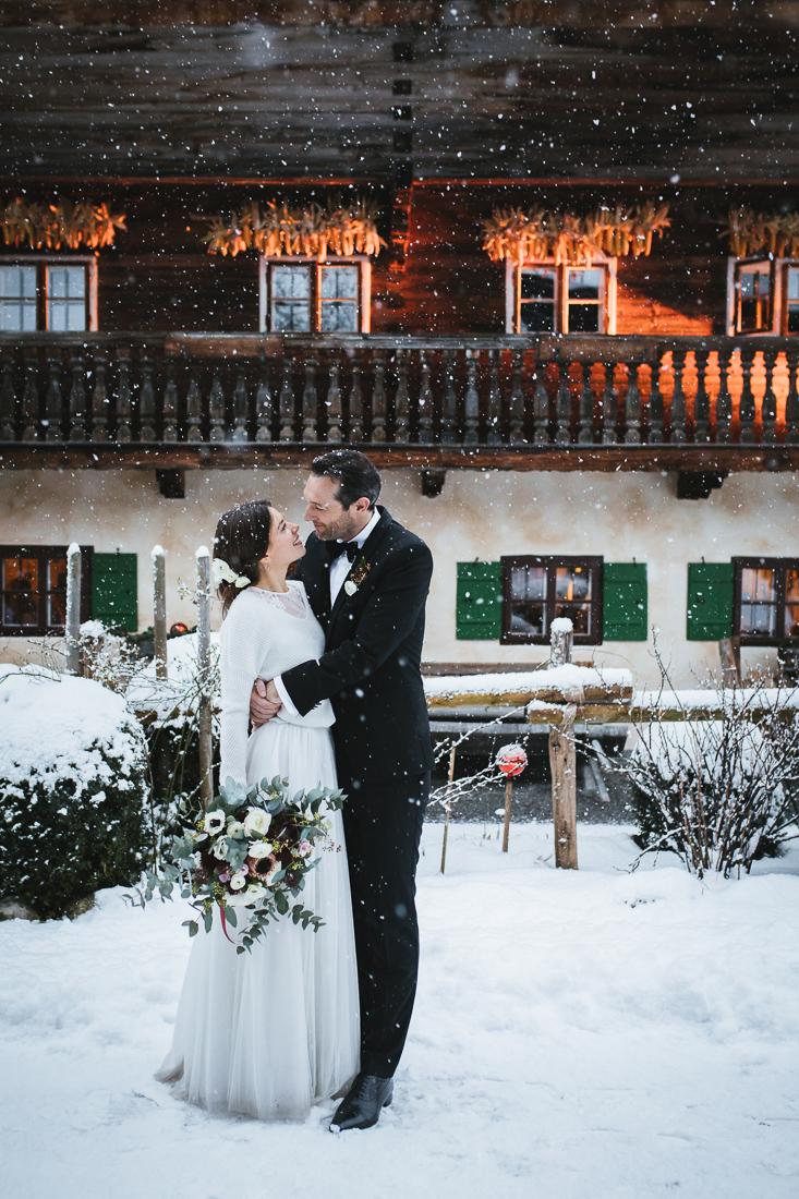 Brautpaar in winterlicher Stimmung vor dem Hasenöhrl Hof stehend mit Schneefall