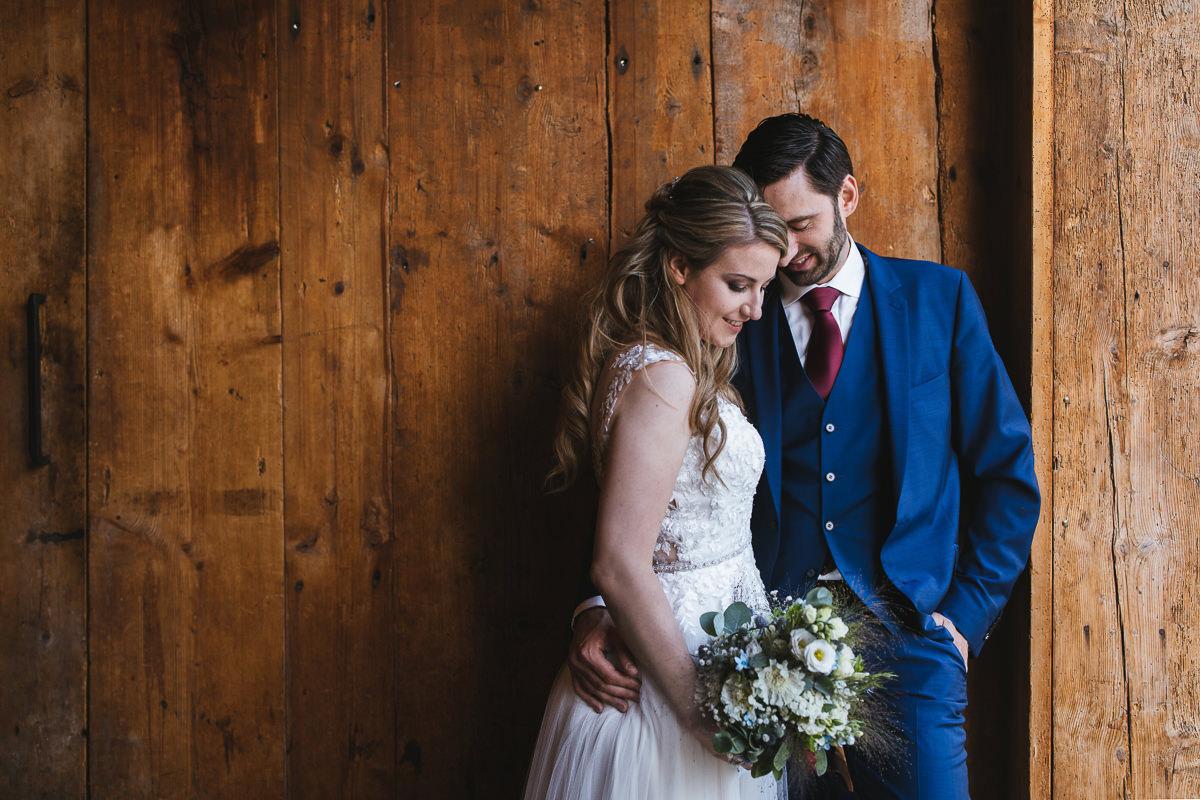 Brautpaar vor einer rustikalen Scheunenwand beim Hirzinger
